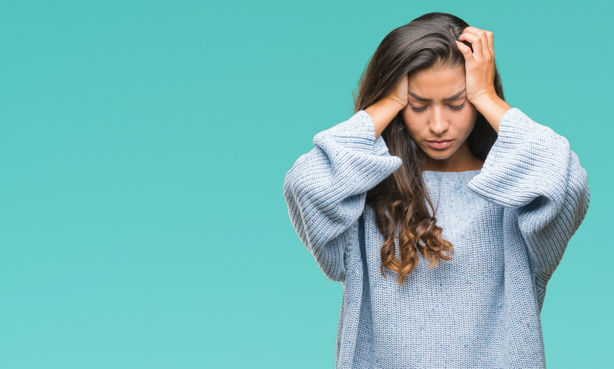 Young beautiful arab woman wearing winter sweater over isolated background suffering from headache desperate and stressed because pain and migraine. Hands on head.
