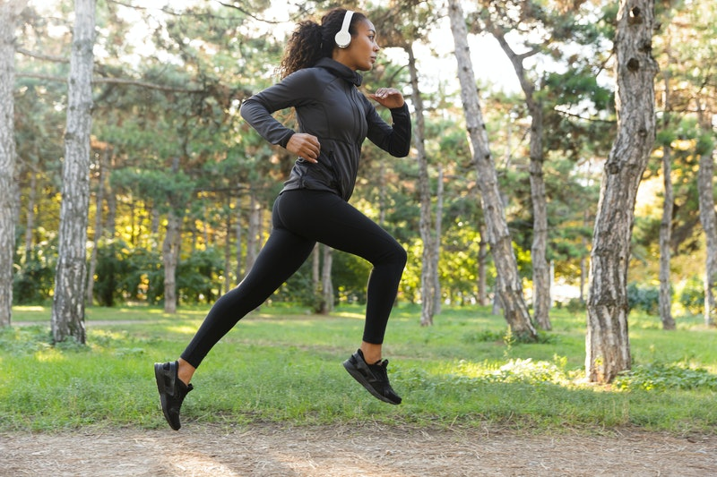 Image of feminine woman 20s wearing black tracksuit and headphones working out while running through green park
