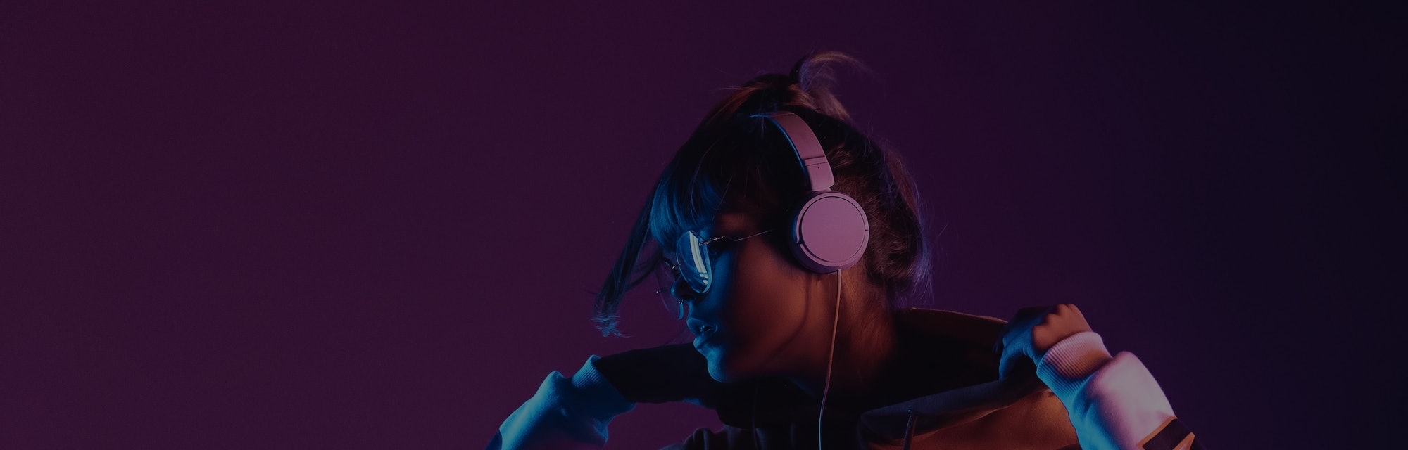 Hipster igen teen pretty fashion girl model wear stylish glasses headphones enjoy listen new cool music mix stand at purple studio background in trendy 80s 90s club blue party light, profile view