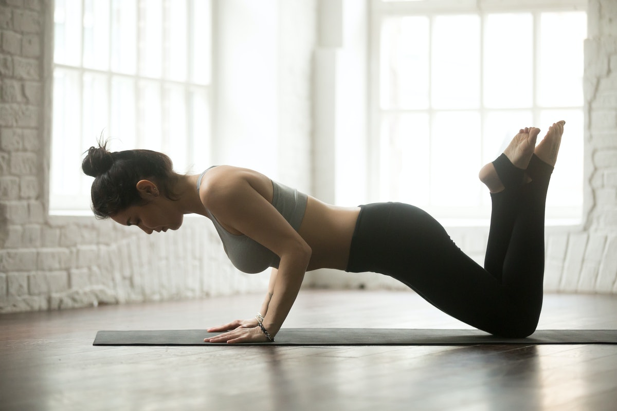A person with her hair tied up on top of her head sinks into a modified pushup at home. Modifying burpees however you need to fit your body doesn't take away their cardio- and strength-building capacity.
