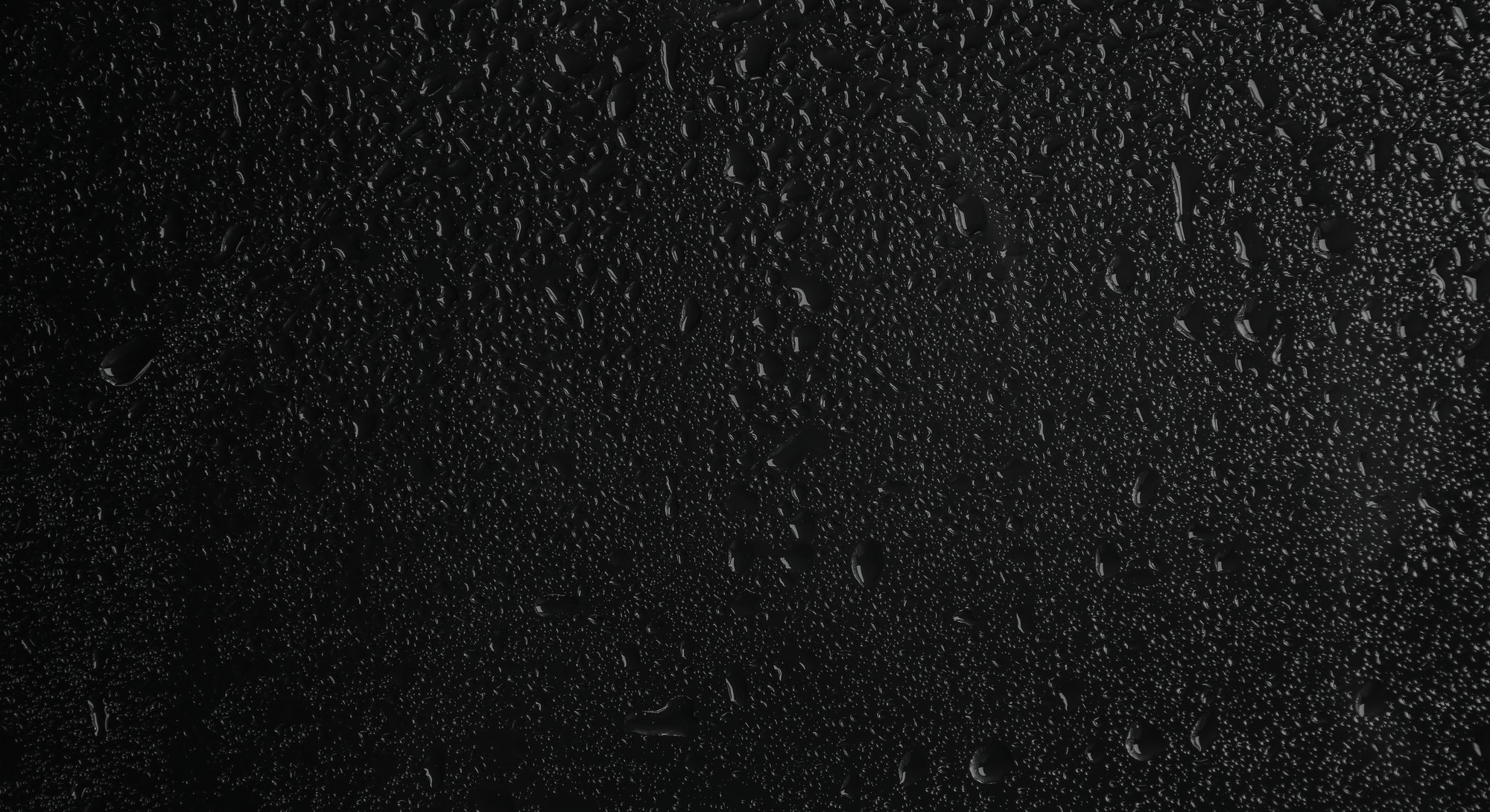 Glass with rain drops against dark background