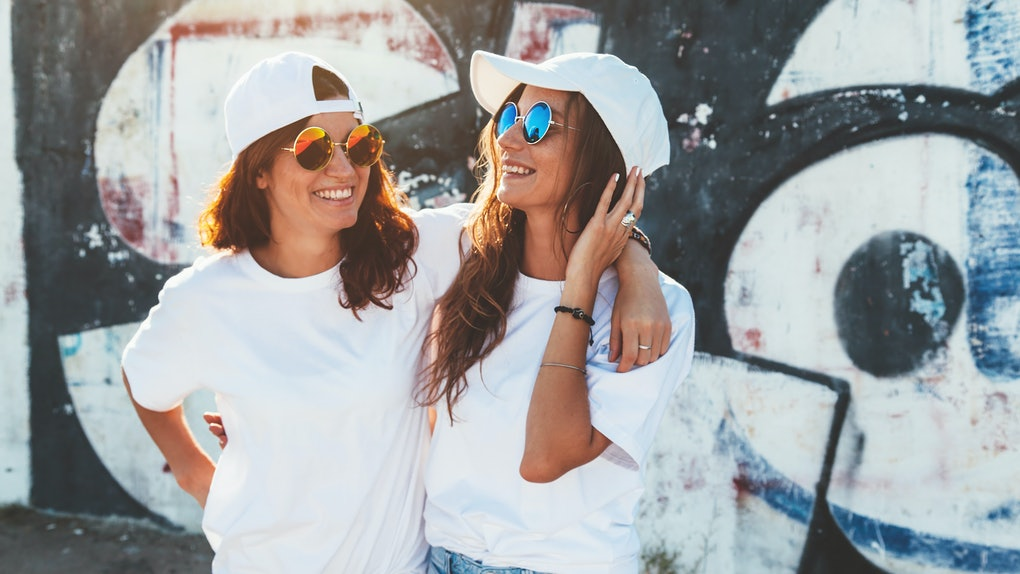 Two women wearing white t-shirts, jeans, white baseball caps, and circular sunglasses laugh while standing in front of a graffiti wall.
