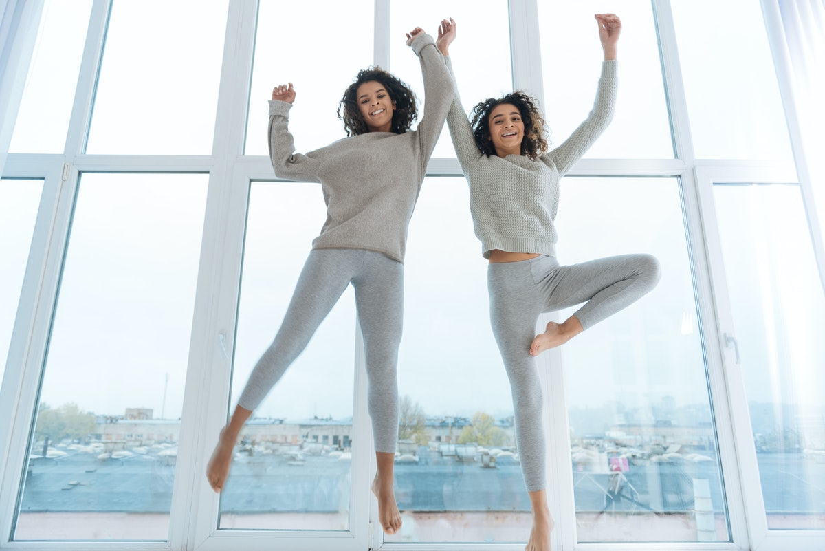 Friends wearing matching grey loungewear jump in front of a large window.