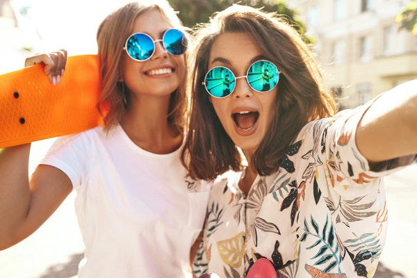 Two trendy girls smile and wear blue round sunglasses while posing for a selfie outside on a sunny summer day.