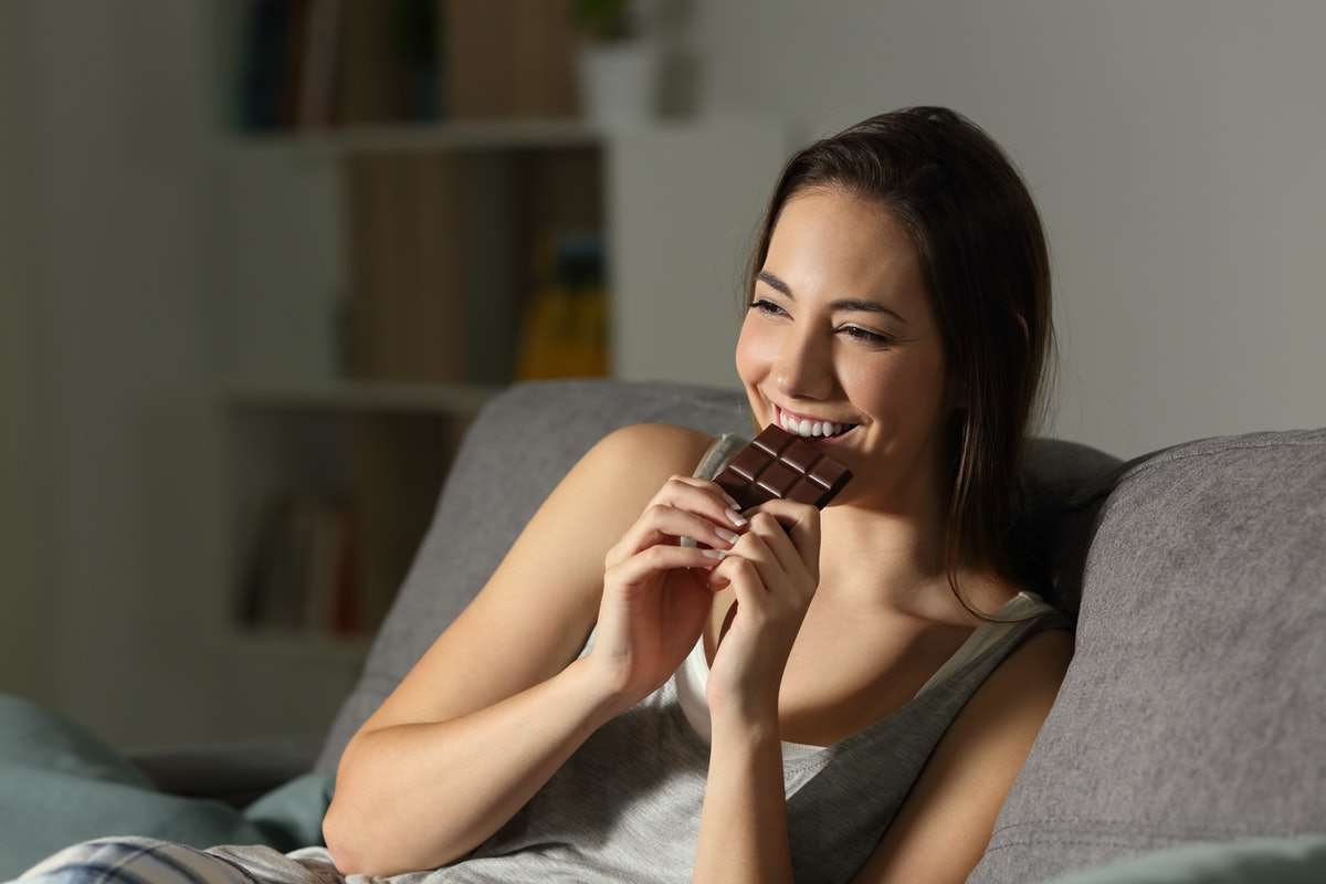 Woman enjoying eating chocolate in the night sitting on a couch in the living room at home