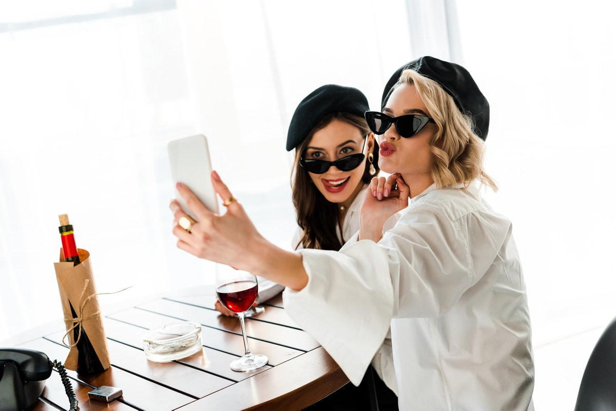 Two elegant women dressed in white button-down shirts, black hats, and sunglasses pose for a selfie at a table while drinking wine.