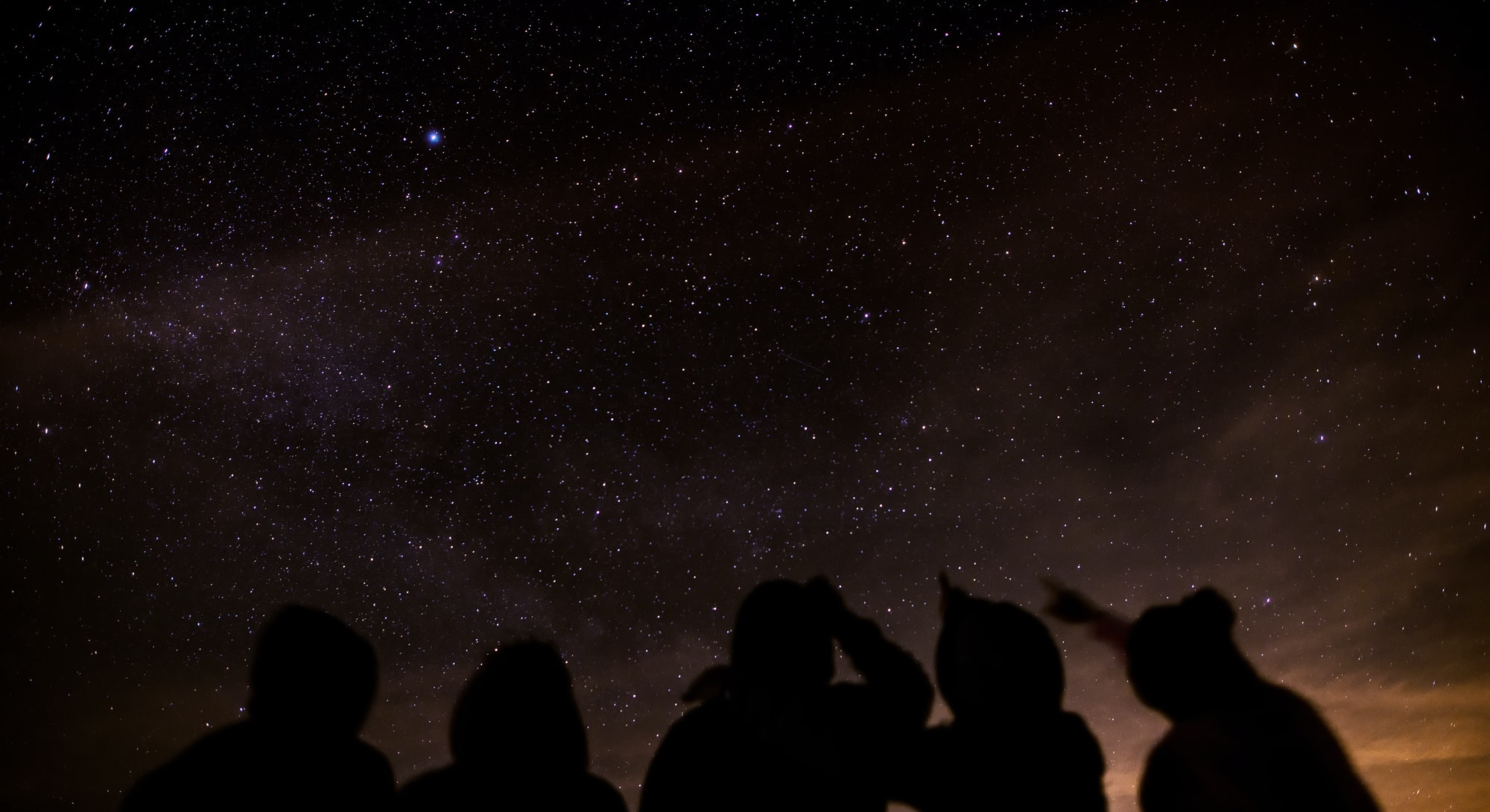 Silhouette of a group of friends stargazing