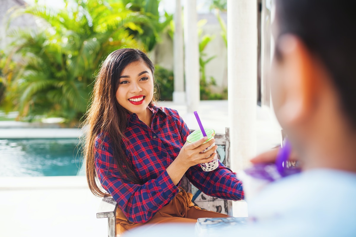 A happy woman relaxes outside on her porch with a bubble tea.