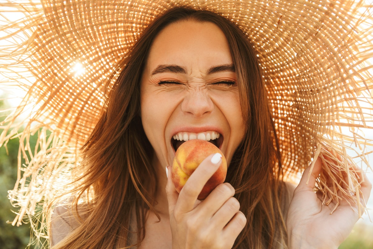 A happy woman wearing a sun hat bites into a peach in a field with the sun behind her.