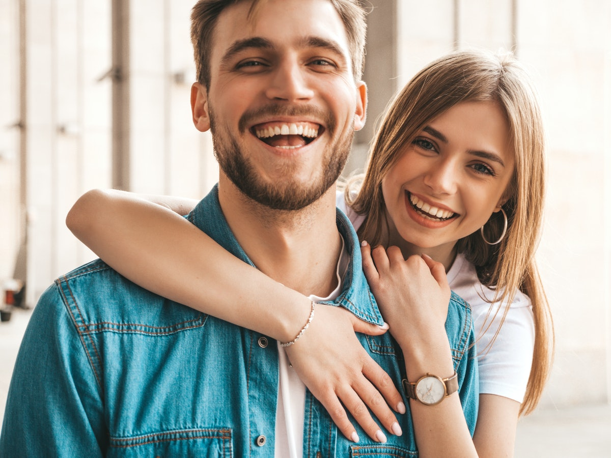 Portrait of smiling beautiful girl and her handsome boyfriend. Woman in casual summer jeans clothes....