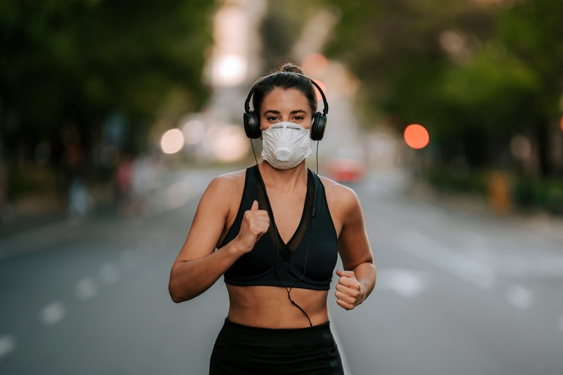 girl does sports with mask on the street during coronavirus