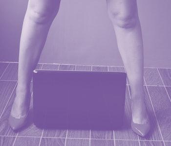 A woman can be seen wearing high heels, she has a laptop between her legs.