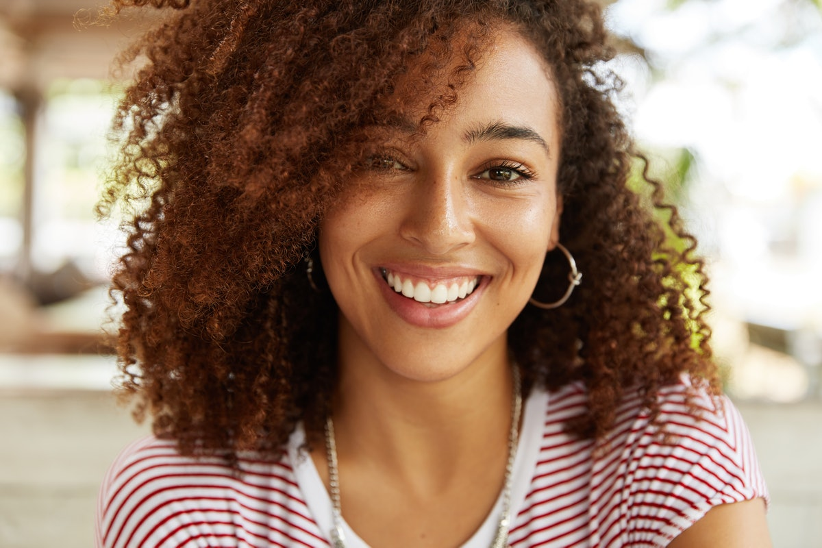 Close up shot of adorable African American woman has broad smile, wears striped t shirt, being in good mood, rests in cafeteria with best friends. Smiling dark skinned young female poses indoor