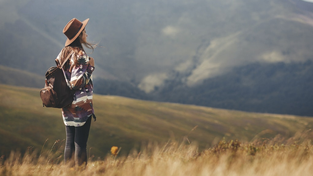 Stylish hipster girl in hat walking on top of mountains. Happy young woman with backpack exploring sunny mountains. Travel and wanderlust concept. Amazing atmospheric moment
