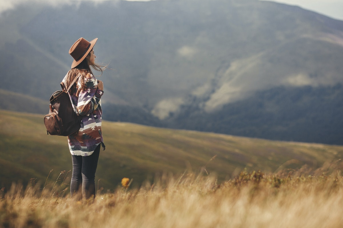 Stylish hipster girl in hat walking on top of mountains. Happy young woman with backpack exploring s...