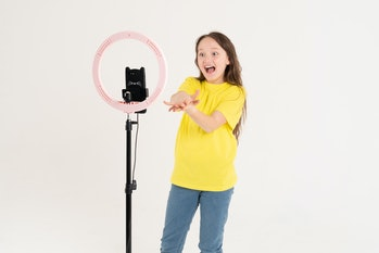 A teenage girl dances and shoots a video. Selfies. The phone is mounted on a tripod and the ring lamp shines.