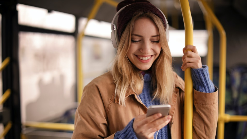 A happy woman wearing a beanie and jacket smiles while she texts on the subway.