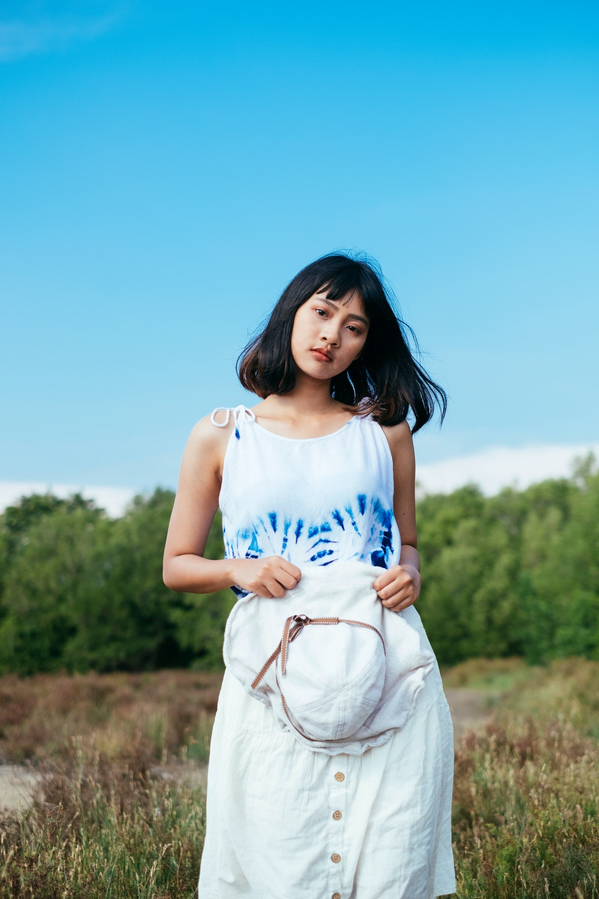 A young Asian woman wears a tie-dye tank top while standing for a photo in a grass field on a sunny day.