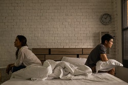 Asian couples quarrel sit in bed ,they argue not to talk to each other. They are unhappy