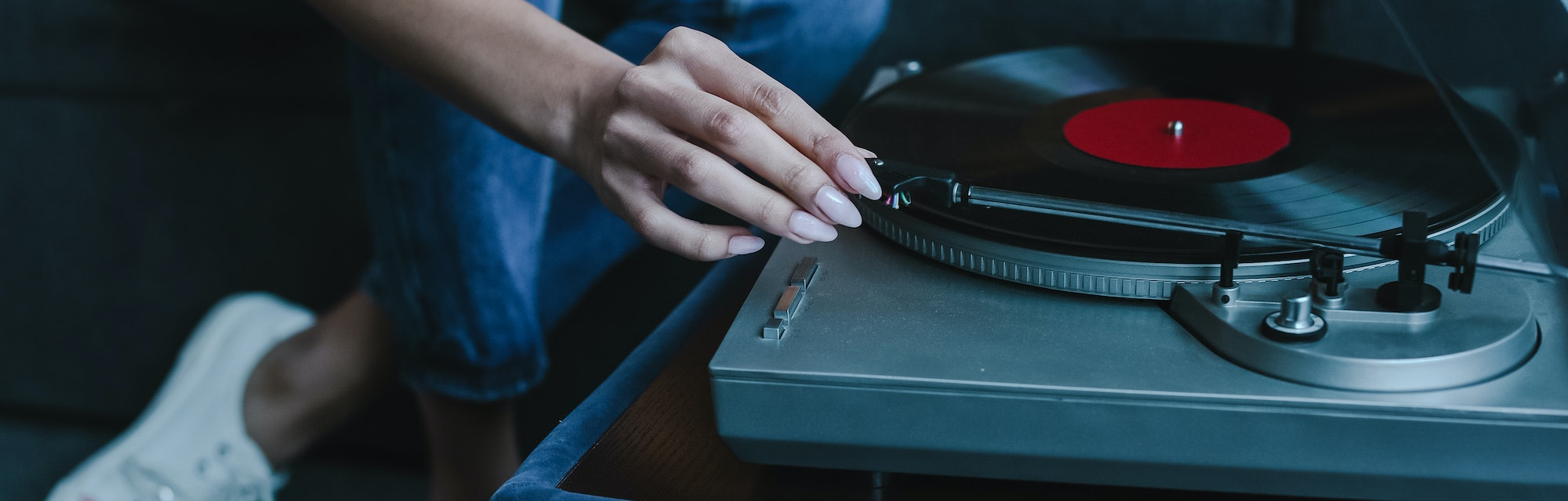 cropped image of mixed race girl turning on gramophone with retro vinyl at home