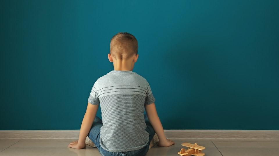 Little boy sitting near dark wall in empty room. Autism concept