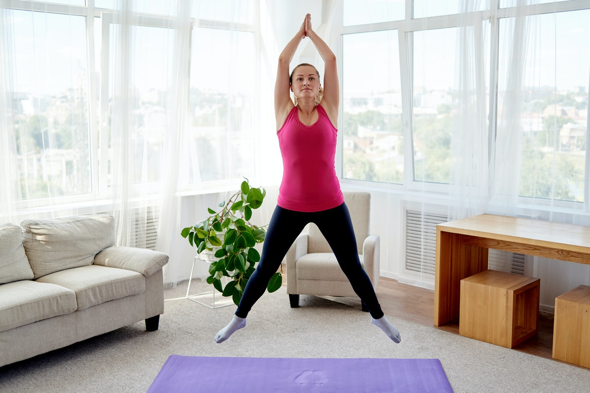 A person wearing a pink tank and black leggings jumps up during her living room workout. Burpees are an excellent small space cardio workouts.