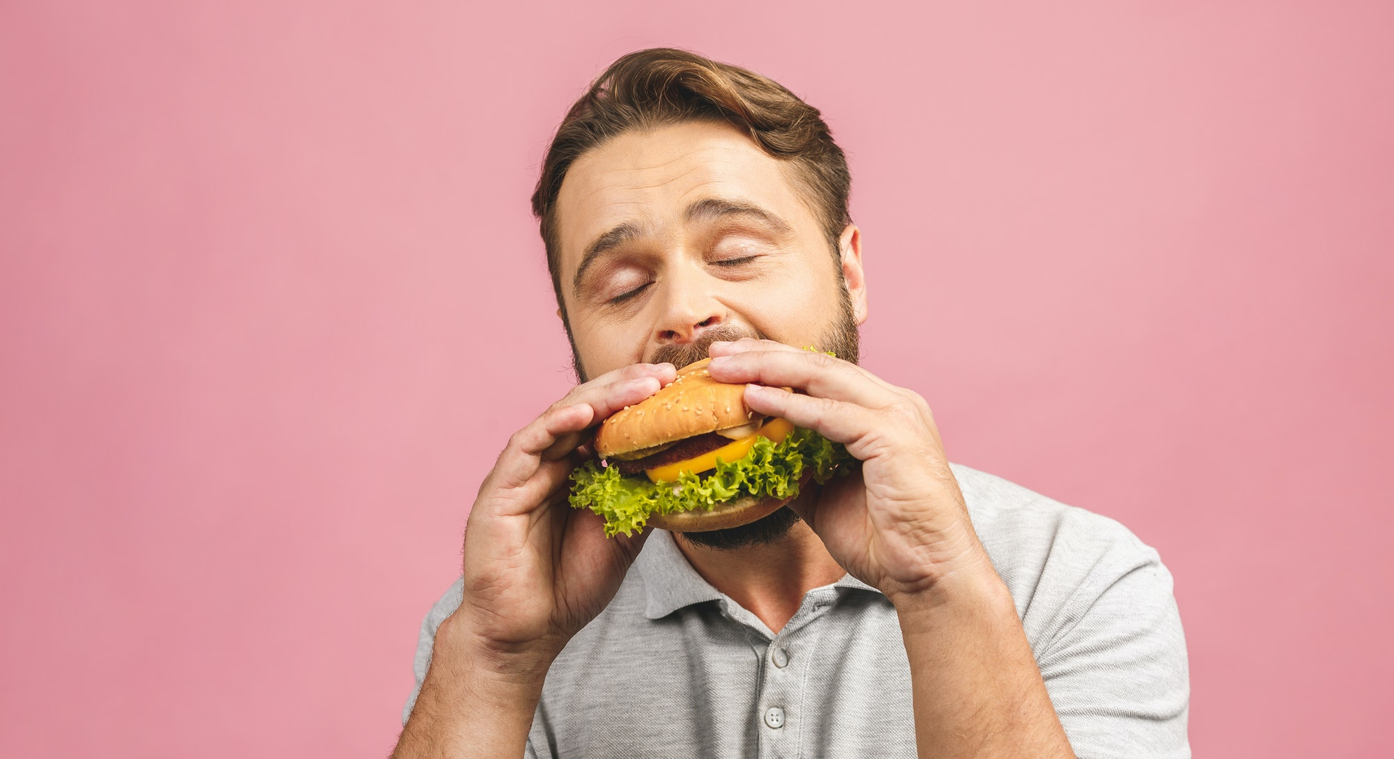 Young man holding a piece of hamburger. Bearded gyu eats fast food. Burger is not helpful food. Very...