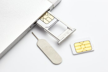 two sim card and sim card tray and sim card eject tool put nearly sim card tray slot on white background