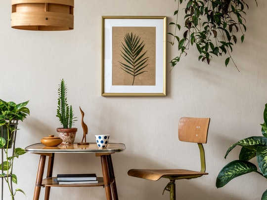 Retro interior design of living room with stylish vintage chair and table, plants, cacti, personal accessories and gold mock up poster frame on the beige wall. Elegant home decor. Template.
