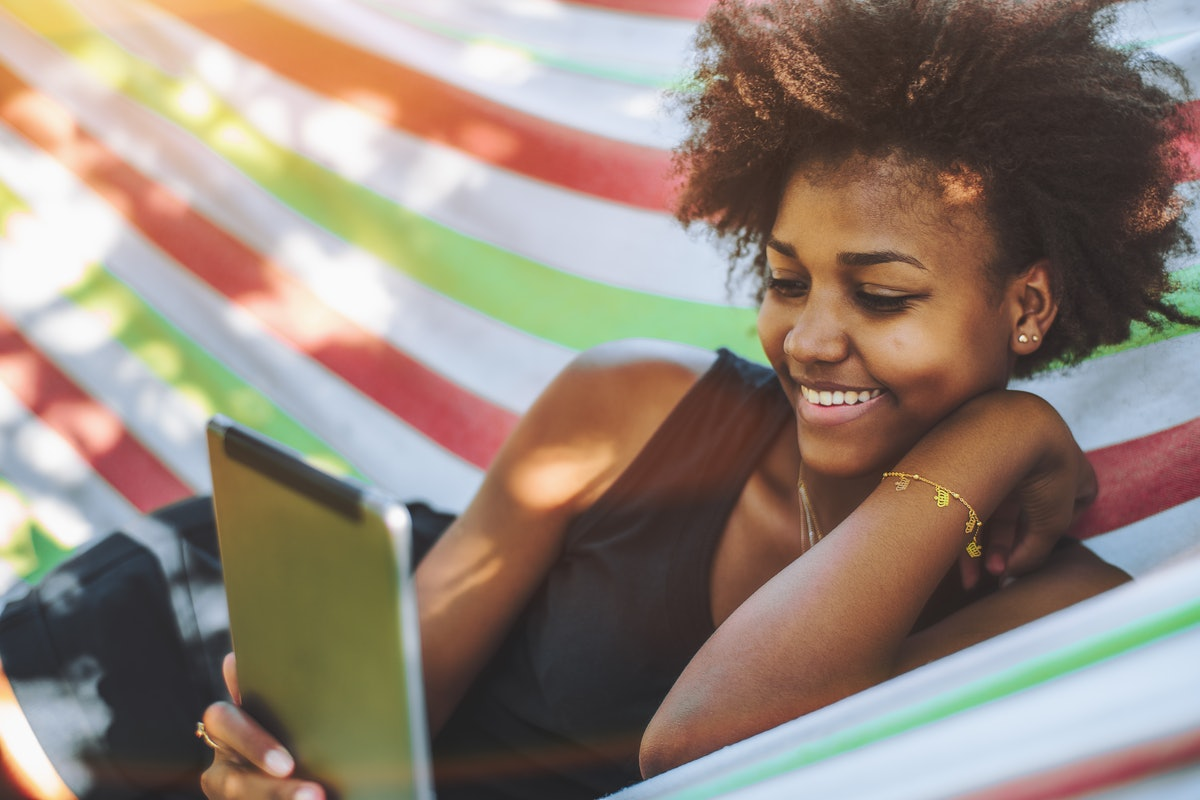 A happy woman reads a book on her tablet while relaxing in a hammock in the sunshine at the beach.