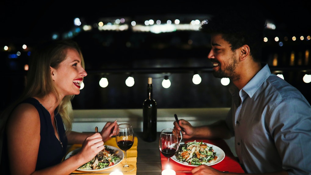 A happy couple laughs while enjoying date night dinner outside.