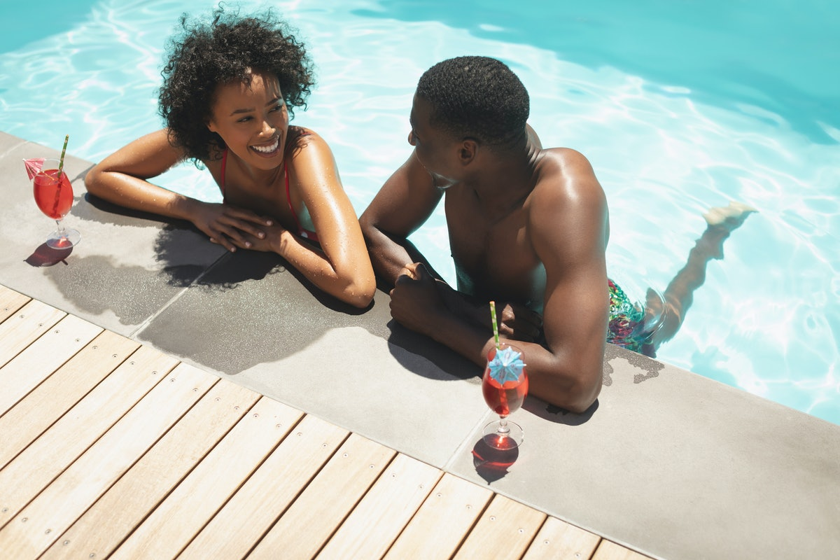 A high angle view of a happy couple relaxing in their pool, smiling at each other on a sunny day, and posing next two two red cocktails.