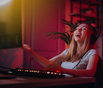 The girl plays computer games at home. A young woman is watching a video in headphones with a microphone. Neon light in the evening. Weekend at home at the screen.Happy and laughing. The girl won.