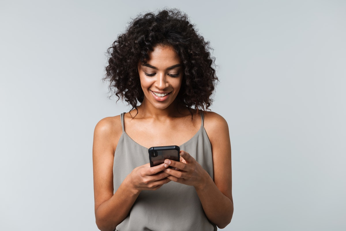 Happy young african woman casually dressed standing isolated over gray background, holding mobile phone