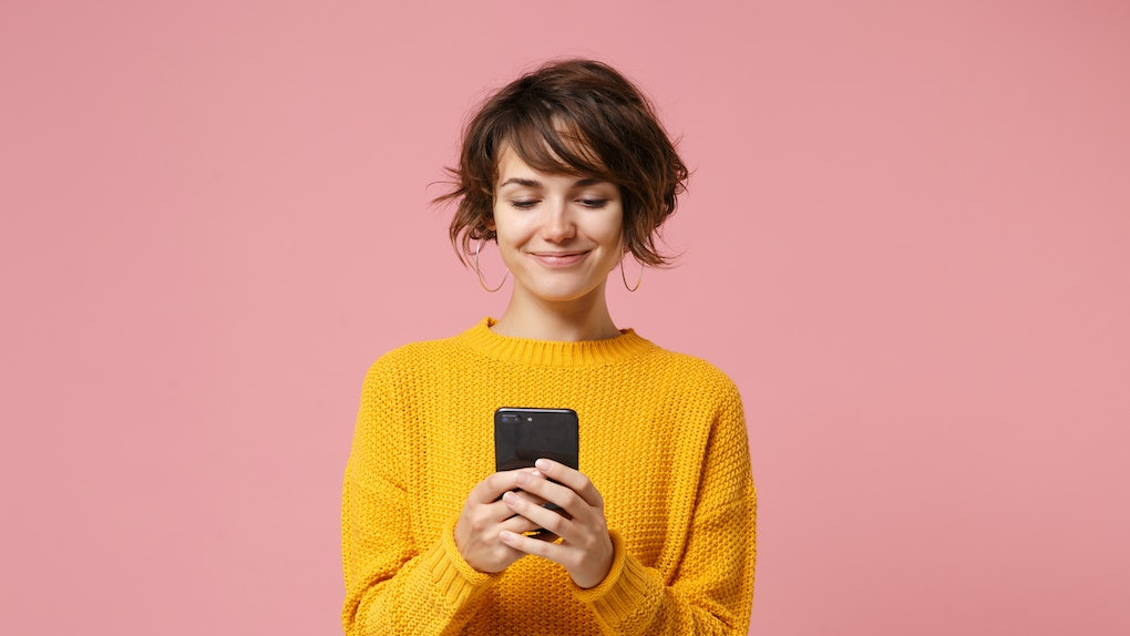 Smiling young brunette woman girl in yellow sweater posing isolated on pastel pink wall background studio portait. People lifestyle concept. Mock up copy space. Using mobile phone, typing sms message