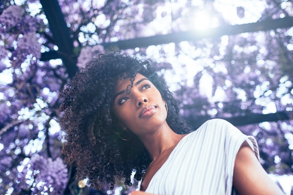 Young black woman surrounded by flowers
