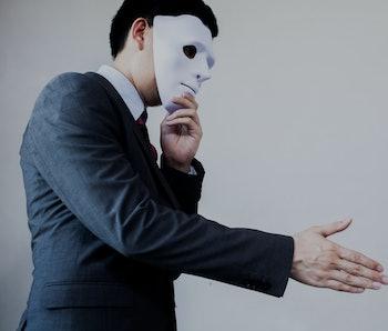 Business man giving dishonest handshake hiding in the mask.