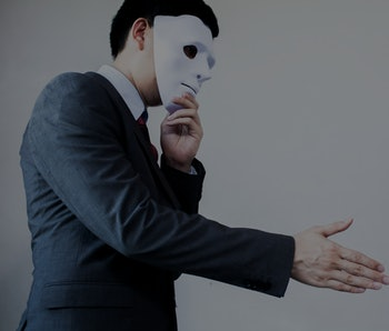 Business man giving dishonest handshake hiding in the mask.