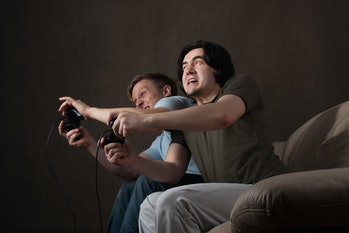 two friends pushing each other while playing video games on gray background