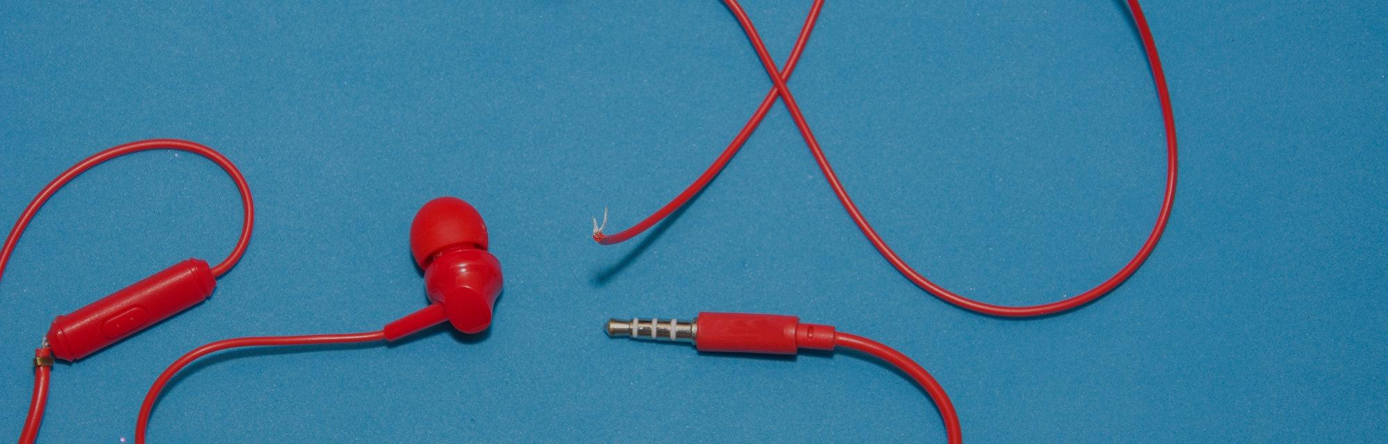 Red broken torn headphones on classic blue background.