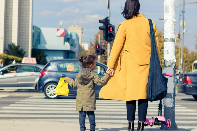 child and grown up holding hands, waiting to cross the street