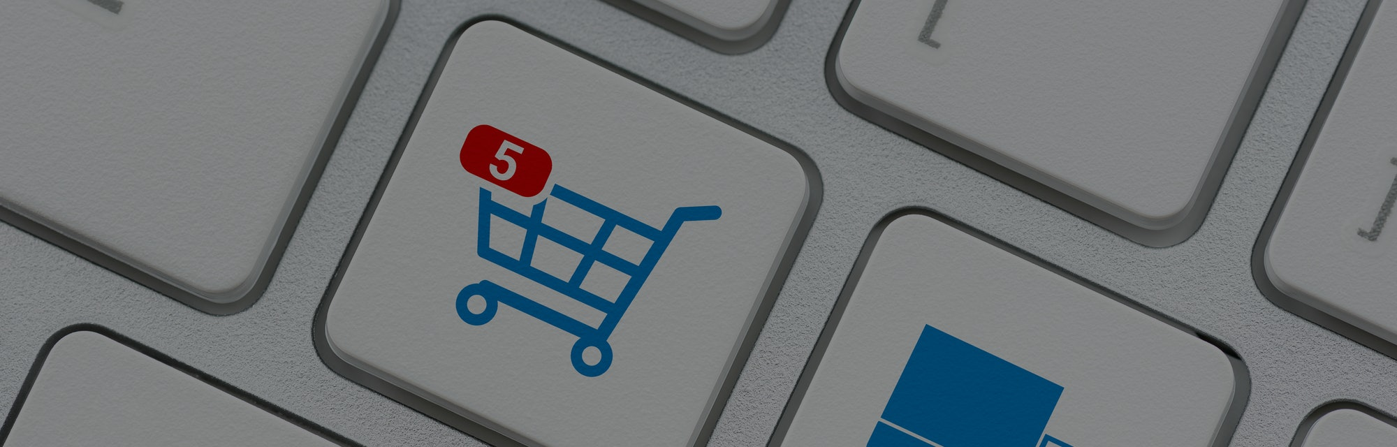 "A white and blue keyboard can be seen with symbols for different types of market actions. One key shows a cart with a red symbol for ""5"" denoting that the user has bought five items for their cart."