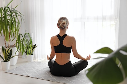 Young woman meditating at home, back view
