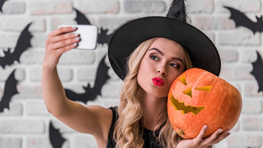 Beautiful blonde girl in black dress and witch hat is holding a scary pumpkin and doing selfie using a smart phone, on background decorated for Halloween