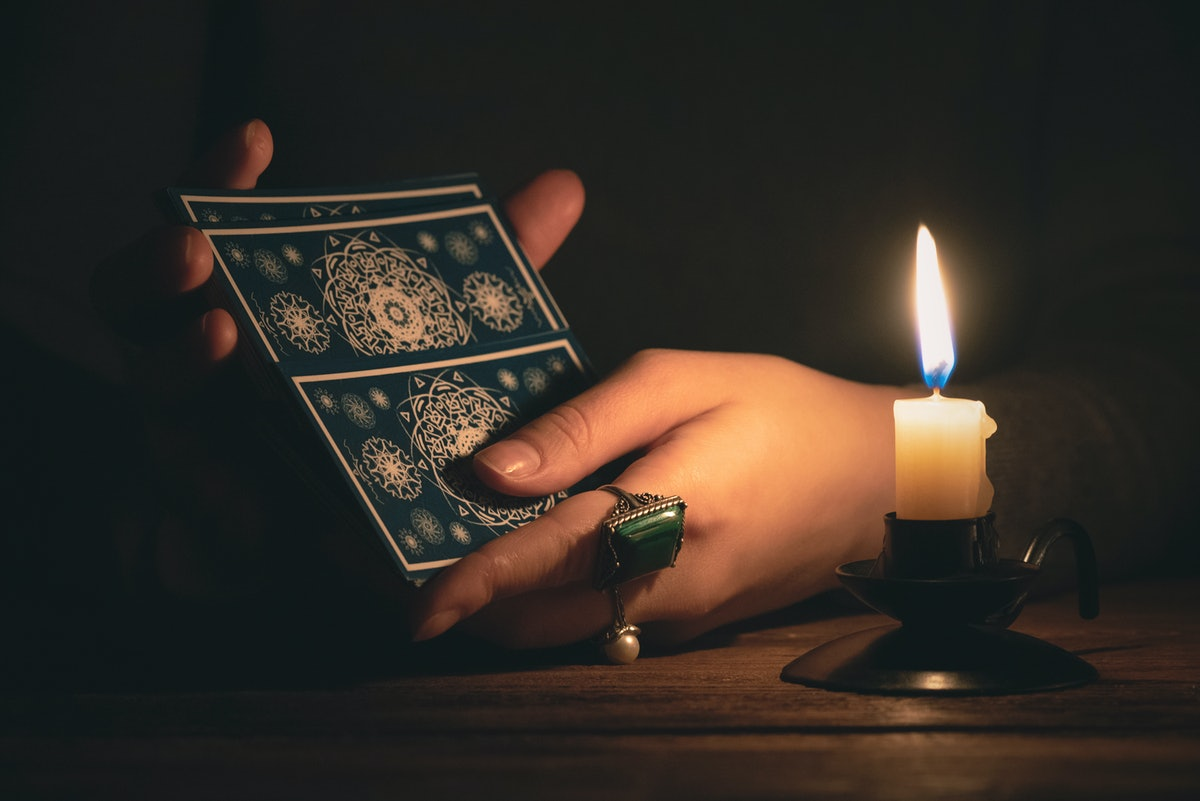 Fortune teller reading a future by tarot cards in the light of candle concept.