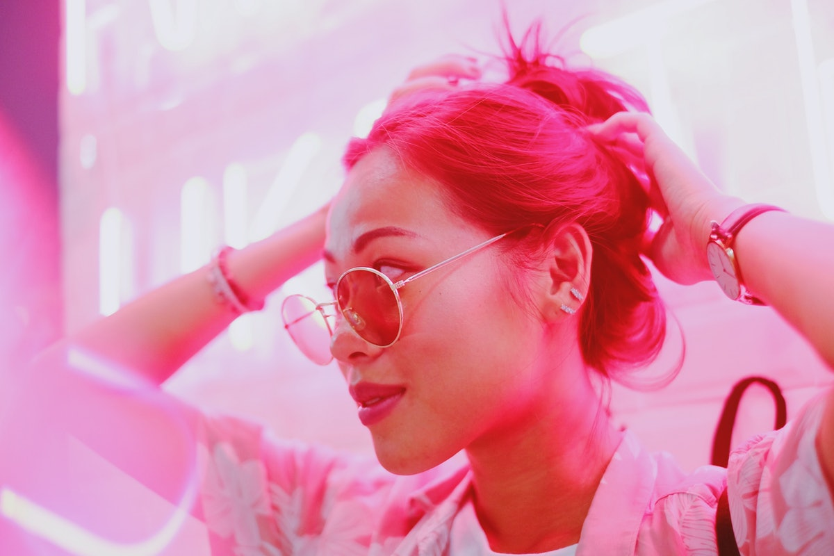 Young asian millennial teen girl in street fashion style with sunglasses, neon light pink background, night life and fashion lifestyle