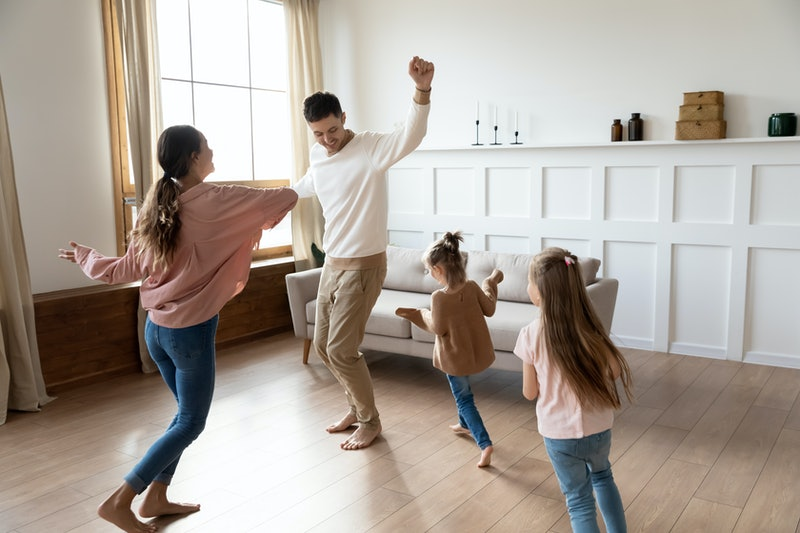 Funny active family of four young adult parents and cute small children daughters dancing together in living room interior, carefree little kids with mum dad having fun laughing enjoy leisure at home