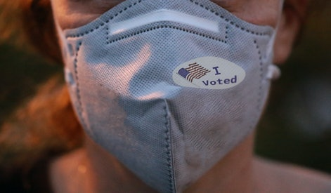 Selective focis on I Voted sticker with USA flag on face mask on caucasian female after voting for president for President