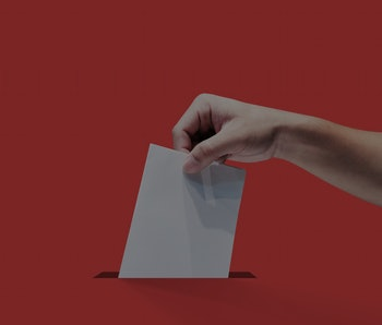 A hand can be seen holding ballot paper for election vote. The paper is white, the background is red.