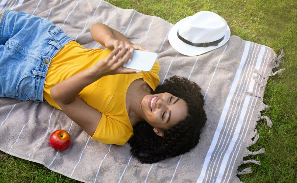 Lovely black woman using mobile phone on picnic blanket outside, top view